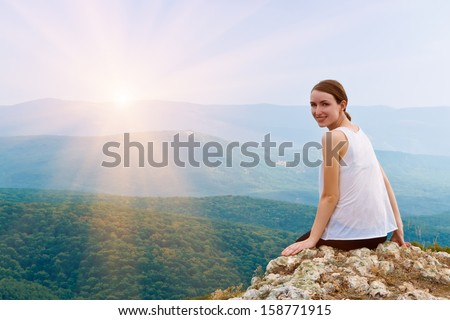 Happy smiling girl sitting on a cliff side. Young woman relaxing in mountains at sunrise