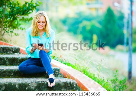 Happy smiling girl sitting on stairs writing a message on her mobile phone on city park background - stock photo