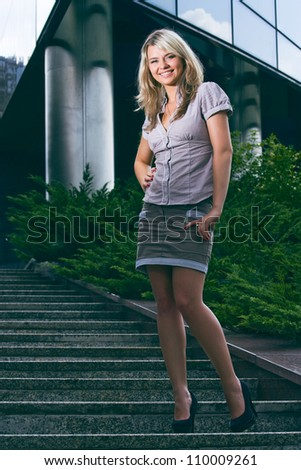 happy smiling girl standing on stairs in front of the modern building - stock photo