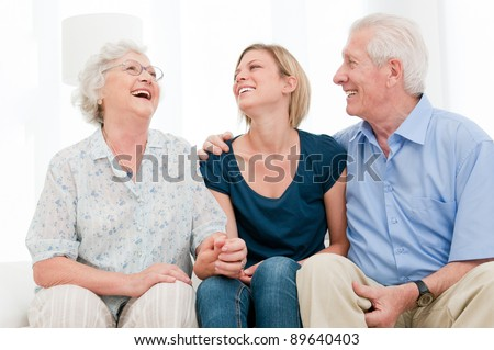 Happy smiling girl staying together with her grandparents at home - stock photo