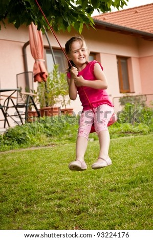 Happy smiling girl swinging on seesaw outdoors (house in the background) - stock photo