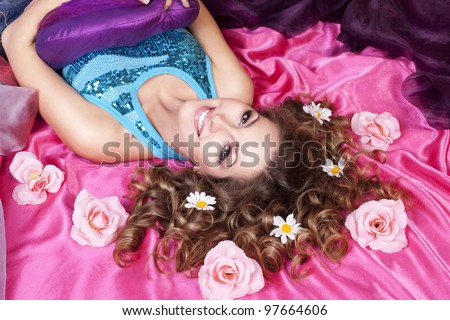 happy smiling girl teenager lying on bed  with pink flowers roses in blonde glossy hair with violet pillow at home in girls room. Morning-evening romantic portrait.