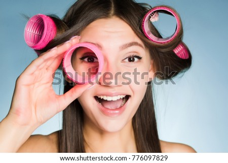 happy smiling girl wants a beautiful hairstyle, holds in her hand curlers