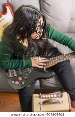 Happy smiling girl ,wearing glasses,learning to play the Bass guitar - stock photo
