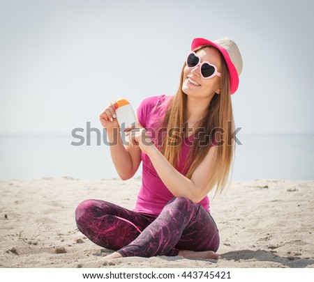Happy smiling girl wearing straw hat and sunglasses in shape of heart on seaside and holding sun lotion, sun protection on beach - stock photo