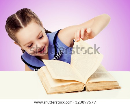 happy smiling girl with a book by the table, against pink studio background - stock photo