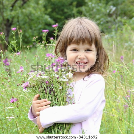 Happy Smiling Girl with Bouquet of Wild Flowers - stock photo
