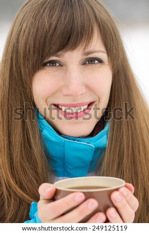 Happy smiling girl with cup of cappuccino at winter outdoor. Beauty caucasian woman holding hot tea - stock photo