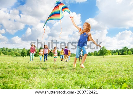 Happy smiling girl with long hair with other kids boys and girls running after her in the park on sunny day - stock photo