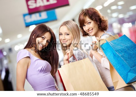 Happy smiling girls in shop with purchases - stock photo