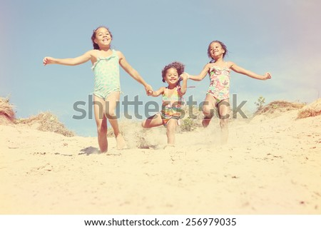 Happy Smiling girls running down the dunes at the beach. Vintage Instagram effect. - stock photo