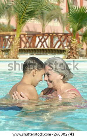 Happy smiling grandma and grandson in blue pool water - stock photo
