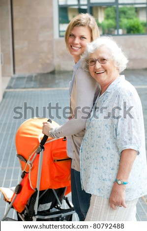 Happy smiling grandmother walking with her grandson and pushing a baby stroller, three generation family outdoor - stock photo