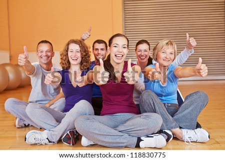 Happy smiling group in fitness center holding their thumbs up in a gym - stock photo