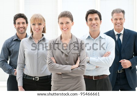 Happy smiling group of business people standing together at office - stock photo