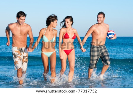 Happy smiling group of friends playing together at beach - stock photo