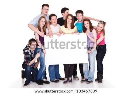 Happy smiling group of friends standing together in a row and displaying a white banner - stock photo