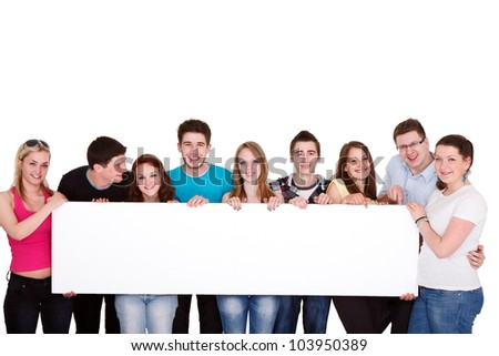 Happy smiling group of friends standing together in a row and displaying a white billboard - stock photo