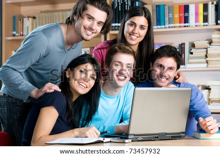 Happy smiling group of friends studying together at college library - stock photo