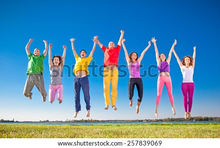 Happy smiling  group of jumping  people on banch of lake in Serbia. - stock photo