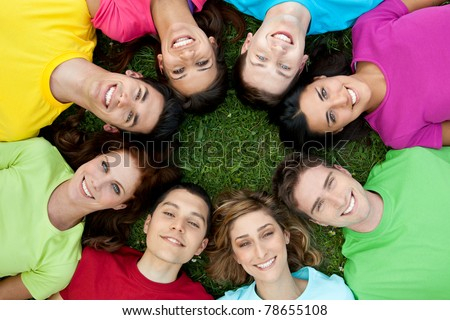 Happy smiling group of young friends staying together outdoor in the park - stock photo