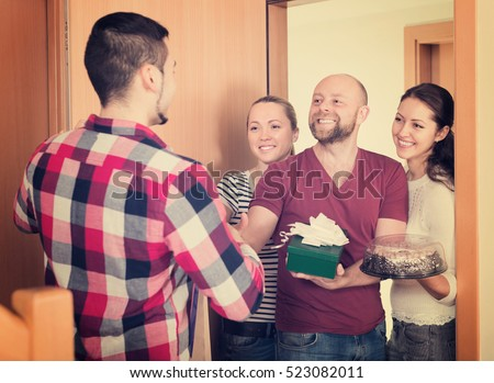 Happy smiling guests with cake and presents standing in doorway. Focus on man