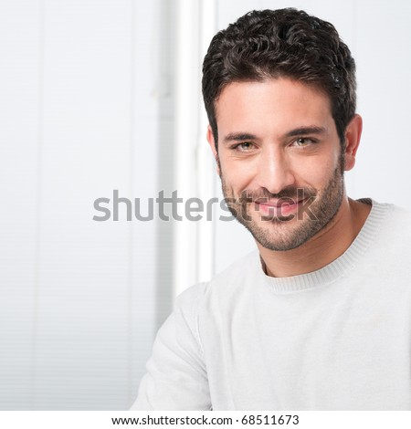 Happy smiling guy looking at camera with satisfaction - stock photo