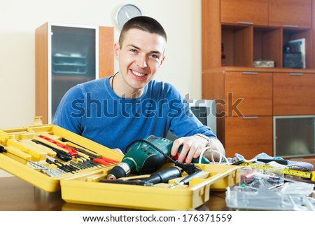 Happy smiling guy organized tools in toolbox sitting by table - stock photo