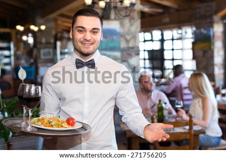 Happy smiling handsome waiter in a restaurant holding a tray with a salad and glasses full of wine in a restaurant - stock photo