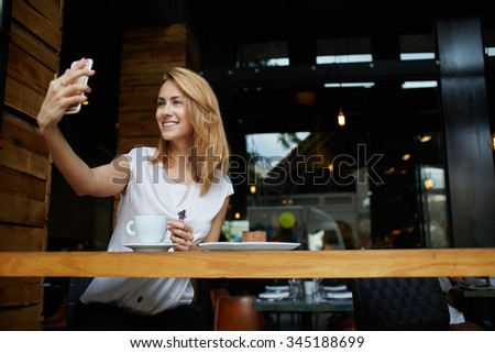 Happy smiling hipster girl making self portrait with mobile phone camera while sitting in modern coffee shop, cheerful woman posing while photographing herself for social network picture, copy space - stock photo