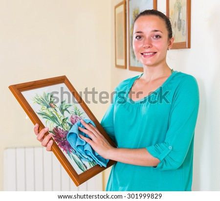 Happy smiling housewife dusting the picture in the gallery - stock photo