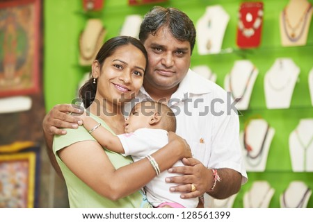 Happy smiling Indian family woman mother man father hugging their little child boy in shop - stock photo