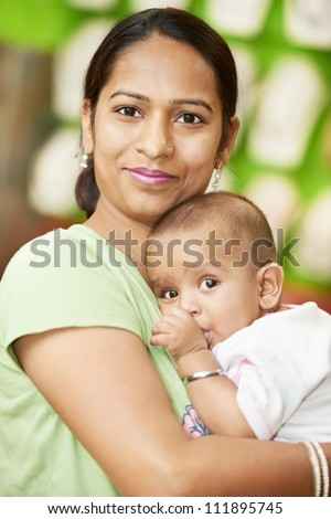 Happy smiling Indian woman mother hugging her little child boy - stock photo