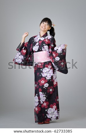 Happy smiling Japanese girl dancing in traditional clothing. - stock photo