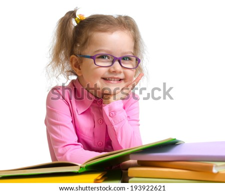 Happy smiling kid girl in glasses reading books sitting at table - stock photo