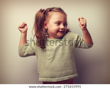 Happy smiling kid girl showing muscular and looking fun. Vintage portrait. Closeup - stock photo