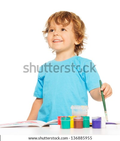 Happy smiling kid painting with paintbrush and colorful vivid colors, smiling - stock photo
