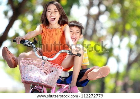 happy smiling kids enjoy riding bicycle together outdoor