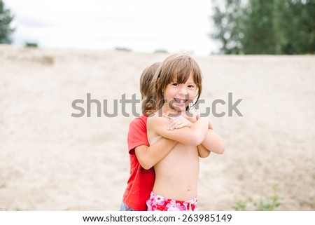Happy smiling kids enjoying their time at the beach. Brother and sister hugging. Fraternal twins having fun during summer vacation. Nice day at the lake. - stock photo
