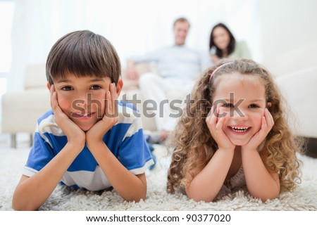 Happy smiling kids lying on the carpet with parents behind them - stock photo