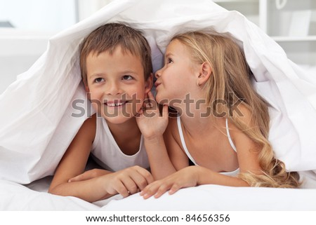 Happy smiling kids sharing their secrets under the quilt - stock photo