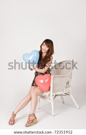 Happy smiling lady holding heart shaped balloon and sitting on chair.
