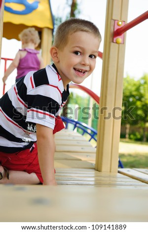Happy smiling little blond boy at playground - stock photo