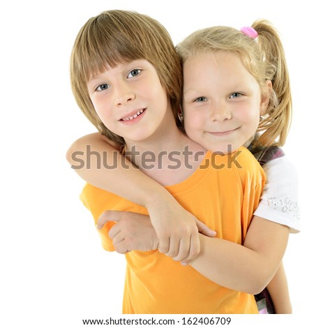 Happy smiling little boy and girl. Portrait of cute embracing little friends over white. Sister hugs brother. - stock photo