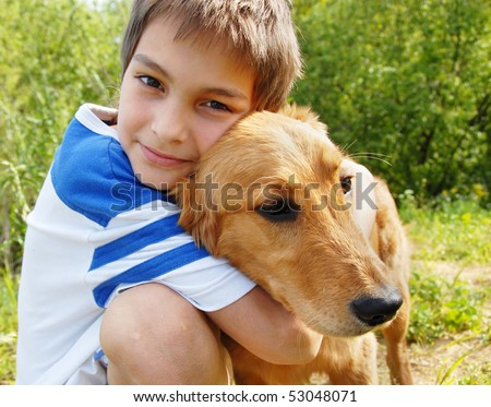 happy smiling little boy hugging his golden retriever dog closeup - stock photo