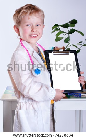 Happy smiling little boy in doctor's uniform with clip board for clinical record in hands - stock photo