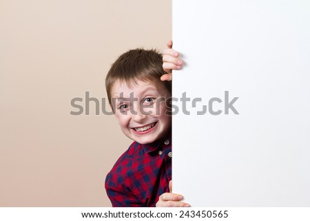 Happy smiling little boy, showing white blank placard, board,poster.Facial expression. - stock photo