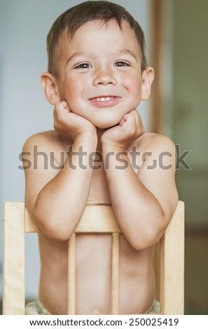 Happy Smiling Little Caucasian Tanned Boy With Hands LIfted. Touching Face. Vertical Image - stock photo