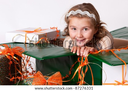 Happy smiling little girl between gifts for Christmas or birthday isolated on white background - stock photo