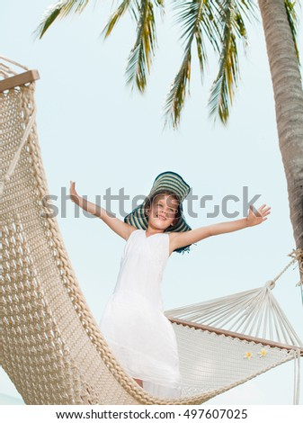 happy smiling little girl child in hammock on the beach